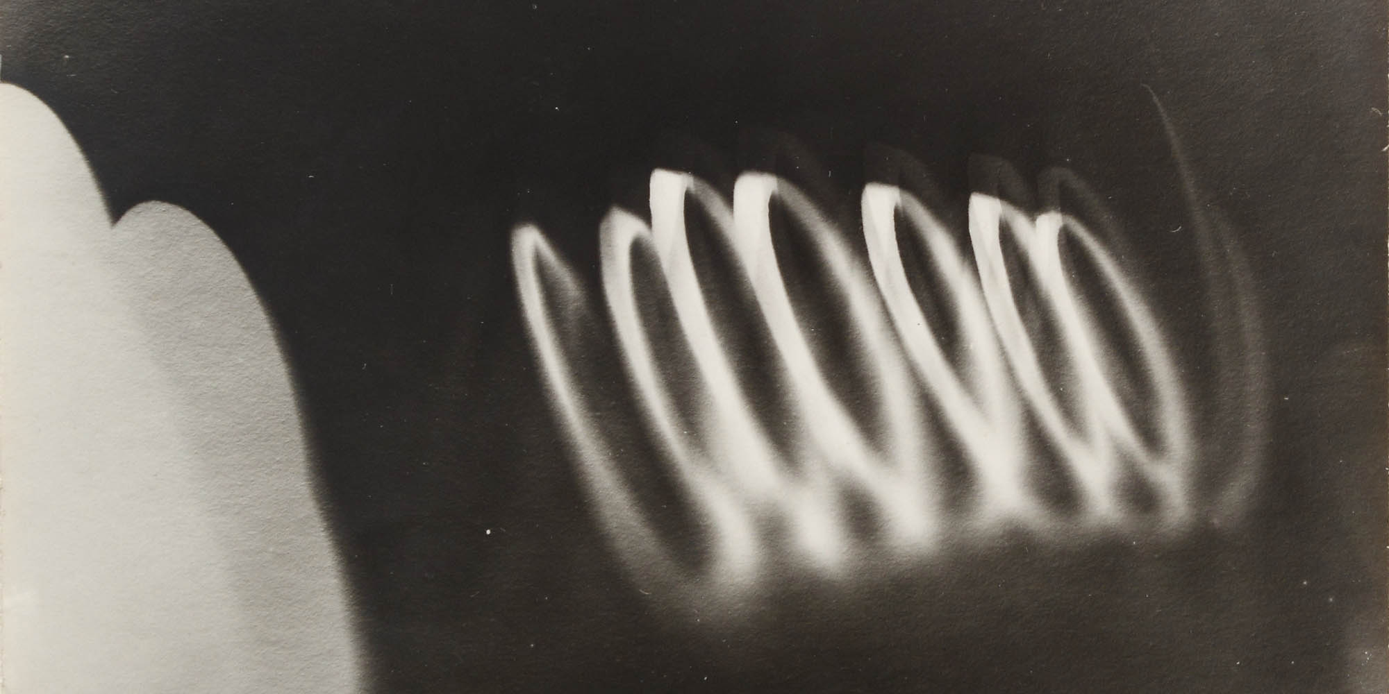 Image of a white coil shape leaning to the left on a black background.