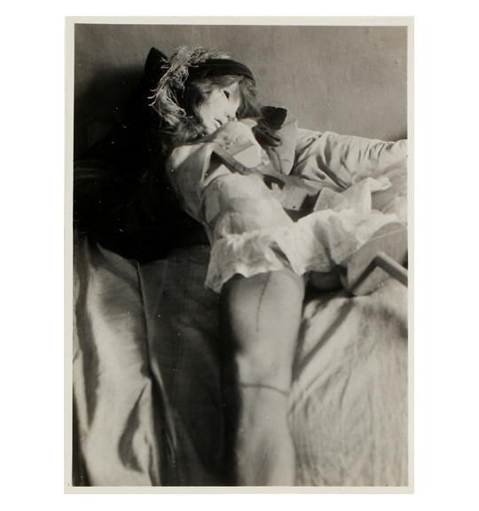 A back and white photograph of a doll or mannequin figure, perhaps laying on a bed. The figure has a mask-like face and hair, with the head facing to the right.