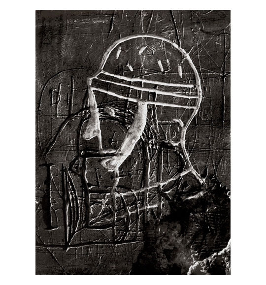 A photograph of what appears to be stone or a wall. The surface has deep scratches or etchings, some lines which are colored white to show a drawing of a man in profile.