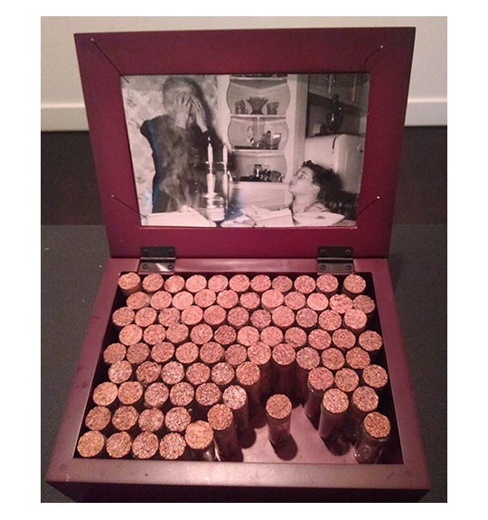 Image of a wood box filled with glass vials. The cover of the box has a photo of the old woman covering her eyes and boy looking at her, perhaps standing in a kitchen.