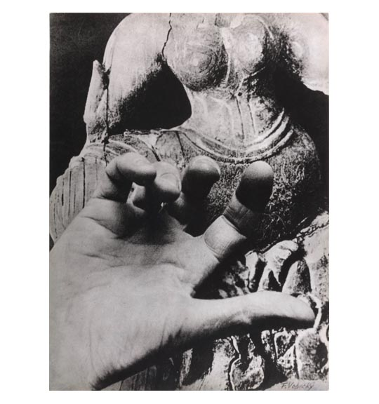 A photomontage of a human hand with the palm facing up and fingers curled inward. A statue of what appears to be stone is placed in the background.
