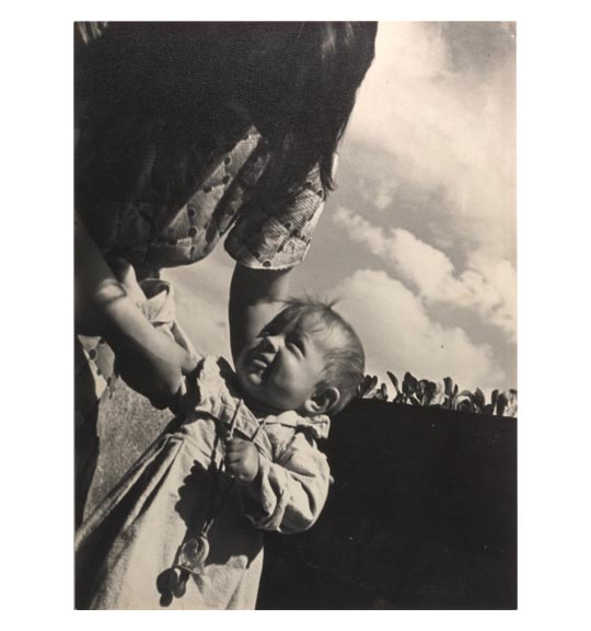 A photograph of what appears to be a woman and child. The woman appears on the left side of the works and holds the child by the right arm. The child looks up at the woman and holds its left hand as if clenched.