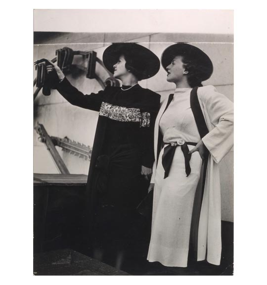 A photograph of two women wearing brimmed hats. One wears a light-colored dress and sleeved garment, and the other wears a long-sleeved black garment. Both figures are looking to the left, and the woman on the left holds up an object, as if in a pointing gesture.