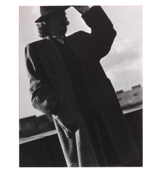 A photograph of a man wearing a hat and a long coat. He is seen mostly in shadow, and holds to the brim of the hat with his left hand, facing the viewer.