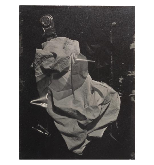A photomontage of various objects. A metal clip-like object appears on the top, under what appears to be crumpled fabric or paper.