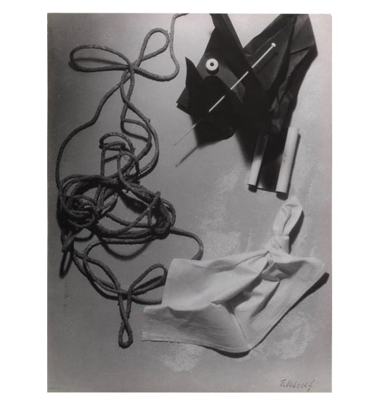 A photomontage of various images, including intertwined rope or twin, what appears to be a knotted handkerchief, and what appears to be black paper or fabric pierced by a knitting needle.