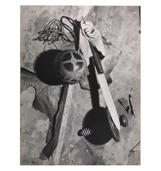 A photomontage of a series of objects, including a sphere, a knife with its blade pointing to the bottom right, a screw-like object, and wire or cable placed on the upper right.