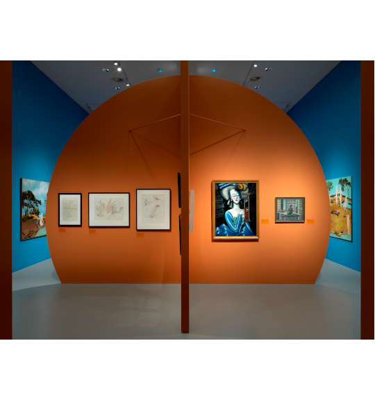 A photograph of an exhibition room with an orange circular wall in the foreground. Three works hang on the left, and two hang on the right. The wall in the background is blue.