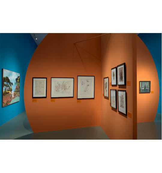A photograph of an exhibition room with an orange circular wall in the foreground. The wall has a corner, and five works are hung on the right wall, and three on the left one. The wall in the background is painted blue, and a large work hangs on the left.