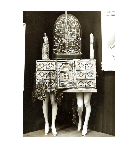 Image of a small chest, which rests on two pairs on mannequin legs, side by side. Dried plant matter hangs off of the chest's drawers on the left side, and two mannequin arms are placed upright on the top of the chest, fingers pointing upwards.