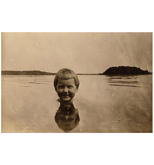 A black and white photograph of a child submerged to the neck in a body of water, with a sky and what appears to be trees in the background.
