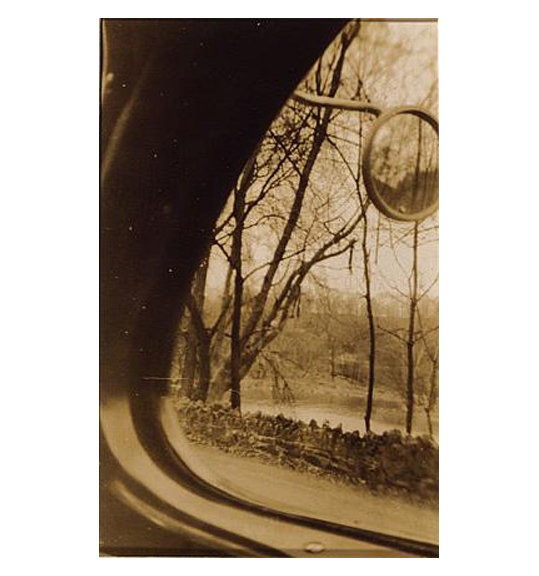 An image of trees and a body of water, seen through what looks like a curved window. A round side mirror appears on the right side.