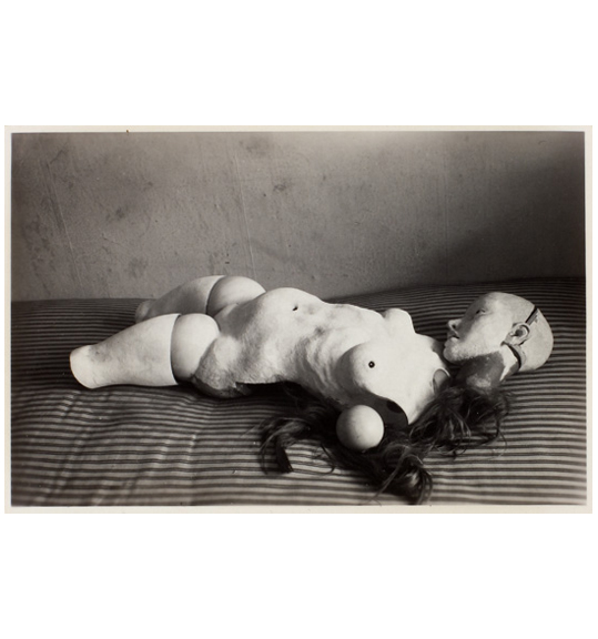 A photograph of a doll like figure laying on a striped surface, perhaps a bed. The digure has dark hair, and is nude with no arms of lower legs.
