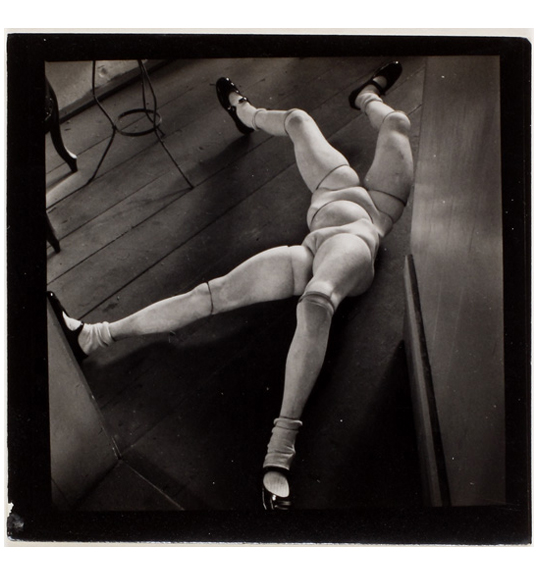 A photograph of two pairs of mannequin legs, joined together by a ball-like joint. The legs are lying on a wooden floor and are wearing white socks and black shoes with a strap.