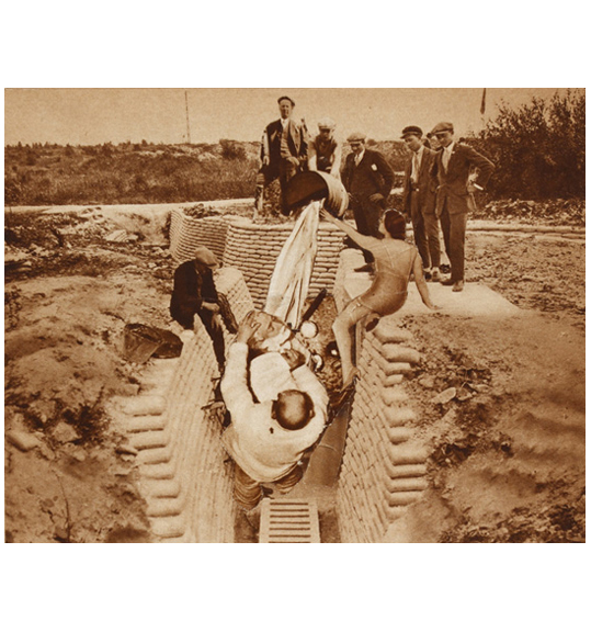 An image of several people gathered about a trench. A woman in a dress and holding a white piece of fabric sits on the right side of the trench.