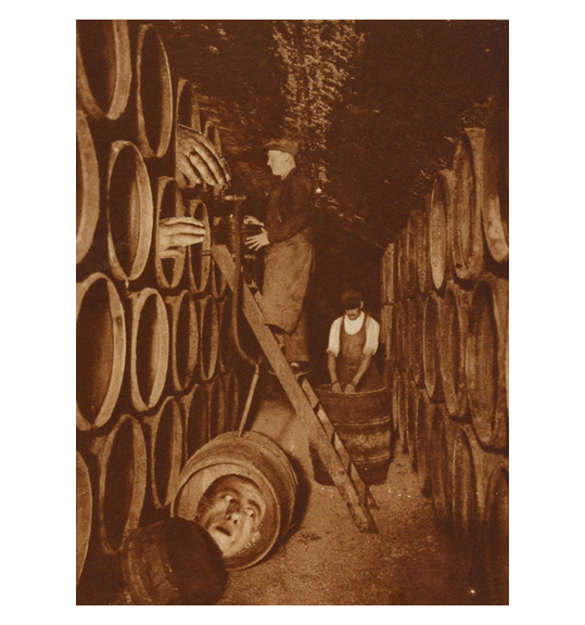 Two men in what appears to be a cellar stacked with barrels. One man stands on a ladder, while two hands reach out of the open barrels as if reaching toward him.
