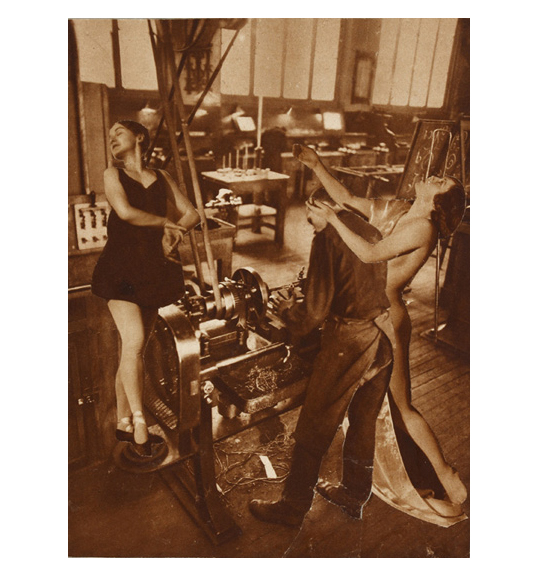 A man in dark clothing and an apron stands in front of what appears to be a printing press of another machine. Two women, standing in dance poses, are placed next to the man, one on each side.