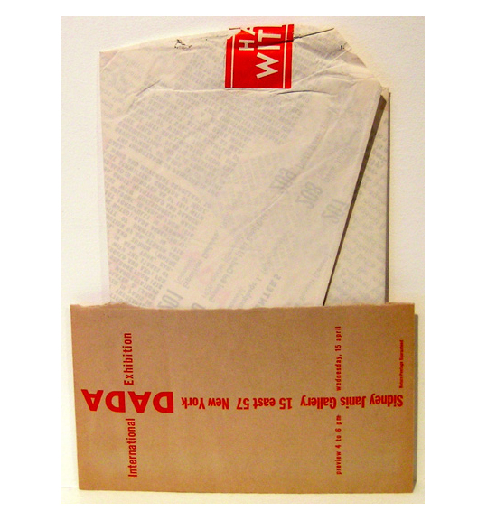 An image of a tightly folded piece of paper with a red sticker or label at the top. A piece of brown paper is placed on the bottom, listing the exhibition details in red font.