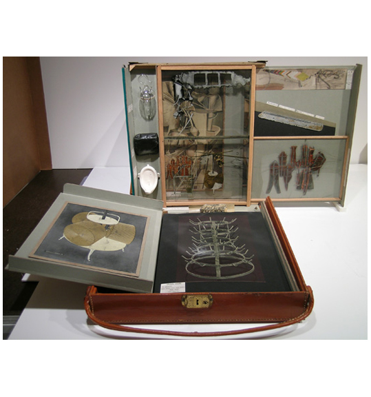 A photograph of a brown leather case with a thin strap, which is opened to reveal shelves. The case also contains framed works and several small objects.