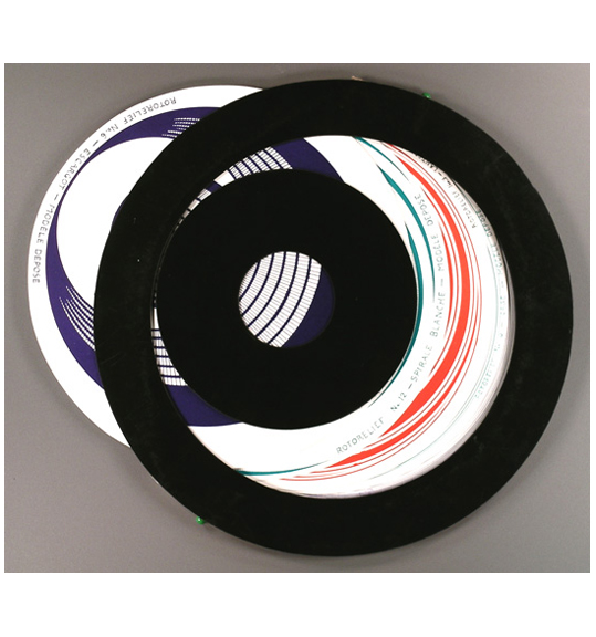 An image of a round shapes with black edges, out of which another disc-like shape emerges. The discs that can be seen have patterns in dark blue, red, and green, with text around the edges.
