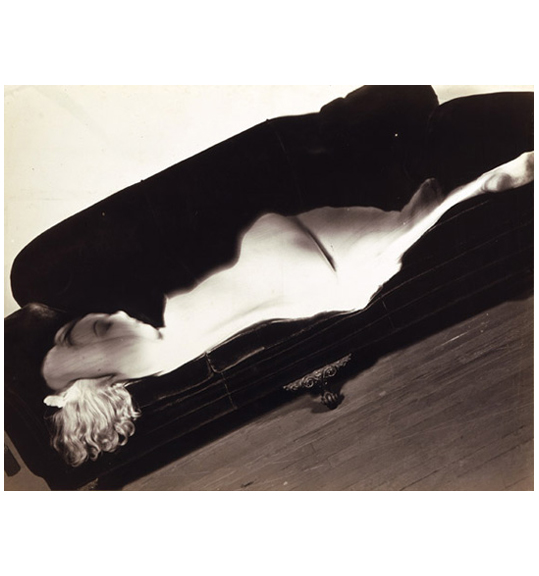 A photograph that shows a titled couch with a woman lying on her side. The woman has blonde hair which hangs over the side of the couch, and she appears to be nude.
