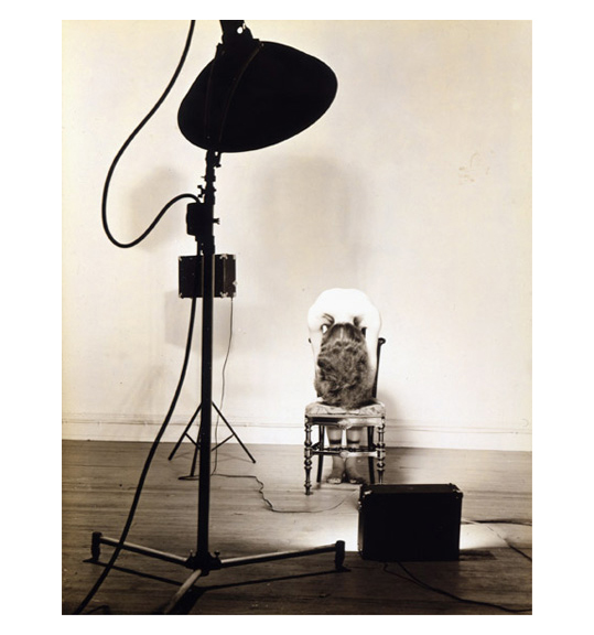 A photograph of a large light or lamp, with a spotlight pointing at a chair. A woman stands as if draped over the back of the chair, with her hair and head almost touching the seat.