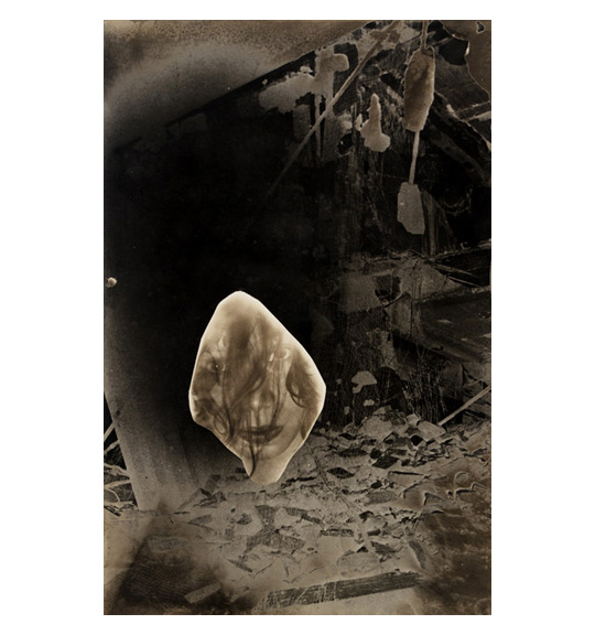 An image of what appears to be a room full of rubble. A diamond like shape appears in the center, with an image of a woman's face on it.