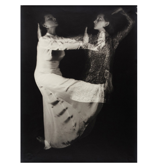 A photograph of two woman wearing long dresses. One woman stands with one foot stretched out and her palms out. The other woman stands in profile, and has her arm bent back and towards her head.