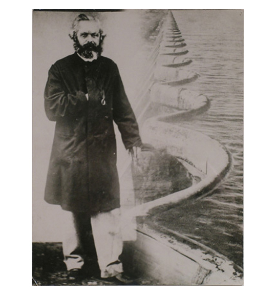 An image of bearded man in black coat and light trousers facing the viewer. The background is a wave-shaped dam, which appears to be holding a body of water.