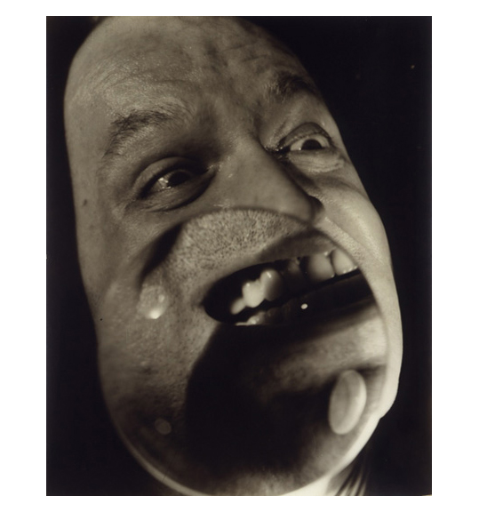 A close-up photograph of a man's face, facing right in three-quarters profile. What appears to be a magnifying glass is placed over the man's mouth, magnifying the lips, gums, and teeth. A close-up photograph of a man's face, facing right in three-quarters profile. What appears to be a magnifying glass is placed over the man's mouth, magnifying the lips, gums, and teeth.