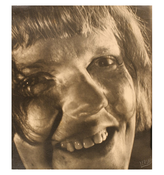 A close-up photograph of a smiling woman with bangs and short strands of hair resting on her cheeks.