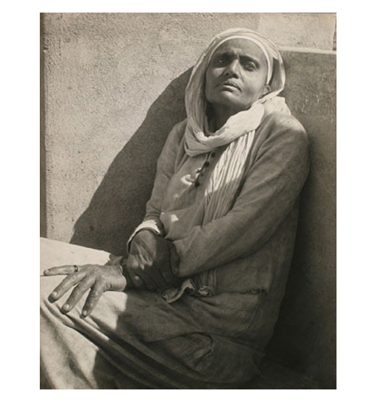 A photograph of a woman sitting with her back against a wall. She wears a white headscarf, which is also wrapped around her neck.
