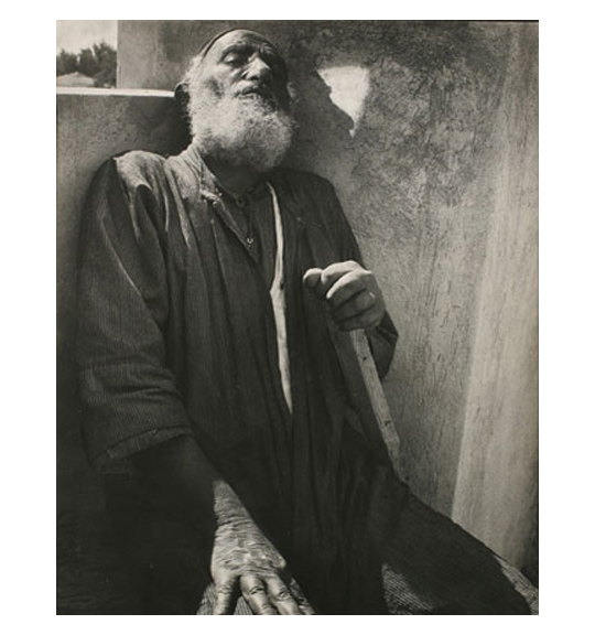 A photograph of a bearded man wearing a dark garment and sitting with his eyes closed. He leans against a wall and rests his left hand on a stick or perhaps a cane.