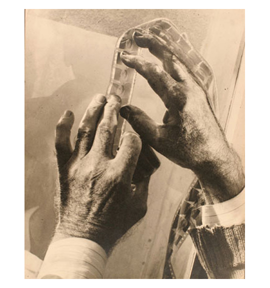 A close-up image of a pair of hands, partially showing the cuffs of a shirt and sweater. The hands hold down a strip of film negatives, which falls over the right hand.