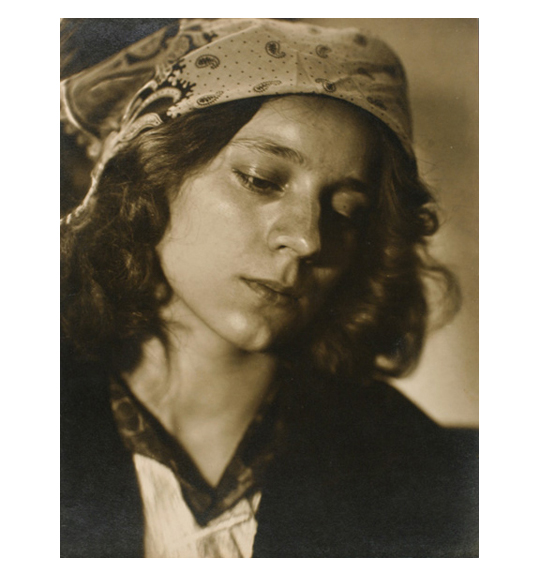 A photograph of a young girl wearing a patterned head scarf with curly hair framing her face. She gazes downwards and to the right.