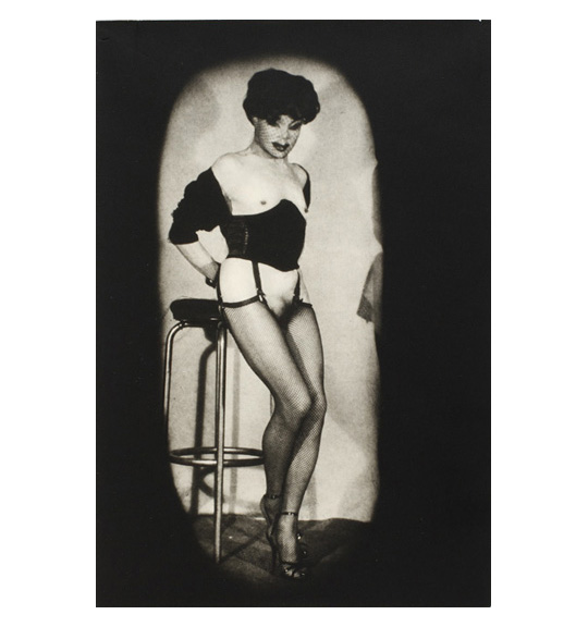 An image of a figure leaning against a stool. The figure wears an under bust corset and stockings. Their face is covered by a lace head piece, and they stand with their hands behind their back.