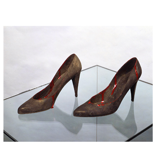 A photograph of bronze high heels sitting on a glass surface. Red liquid, perhaps paint, is dripping down the sides of the shoes.