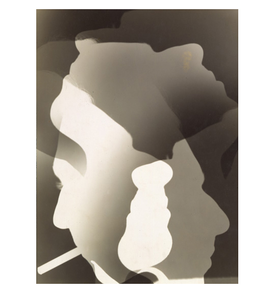 A photograph appearing as if it is a negative, of several overlapping faces in profile looking in different directions. The face on the bottom right has a cigarette in its mouth.