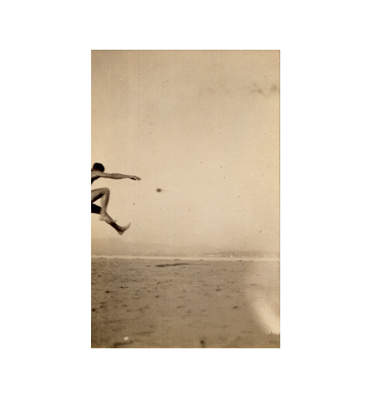 An image of a sky and body of water. The head, arm, and legs of a person, as if in mid-jump, is seen on the middle left of the photograph.