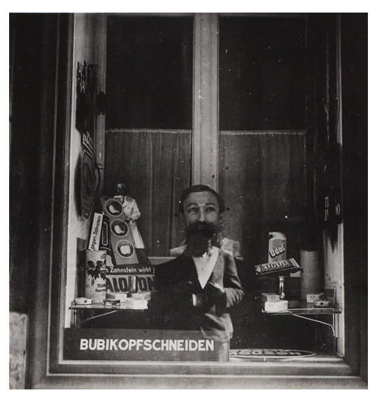 """Black and white image of bearded male figure, perhaps a doll, posed in a window. Several signs in German are placed on a table behind the figure. The sign in the window reads """"BUBIKOPFSCHNEIDEN."""""""
