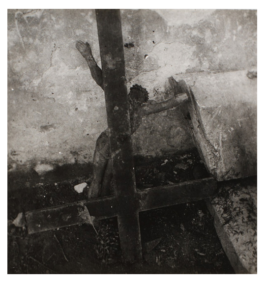 Black and white image of a cross placed upside down on the ground. A figure of Jesus faces the wall and tilts to the right.