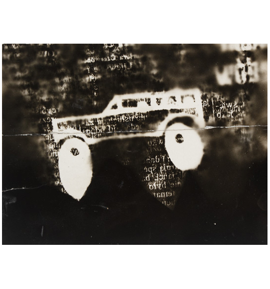 Image of what appears to be a car with large white wheels on a black background. Background seems to have random parts of text and letters.