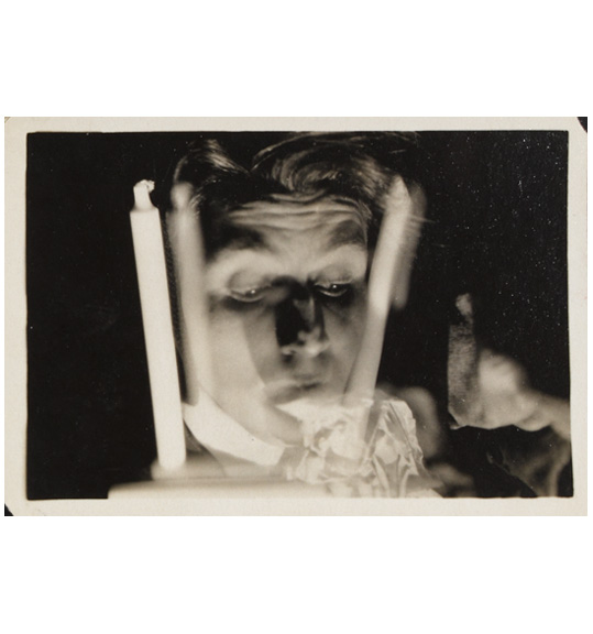 A photograph of a face with eyes looking downward and to the right, with out of focus objects appearing on either side of the head. The objects appear to be white candlesticks.