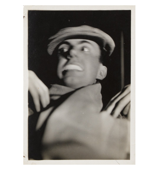 A photograph of what appears to be a man wearing a cap. It appears to be taken from an upward angle, and the man appears to be touching his hands to his shoulders. His mouth is slightly open to show his teeth.