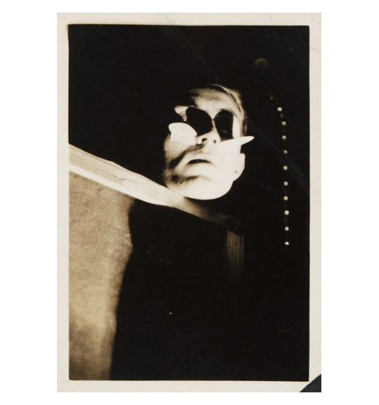 A black and white photograph with a white border. It shows a man's head and face, which is illuminted by a light source. His eyes ar partially obscured, and the rest of his body seems to be hidden behind a panel.