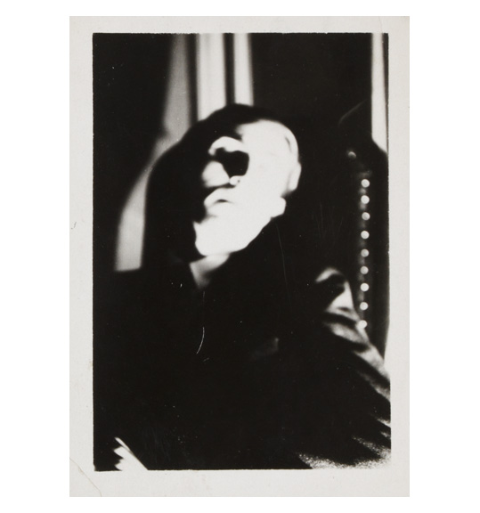 A slightly blurred photograph of a person, perhaps a man. The figure appears to be sitting in an high-backed chair.