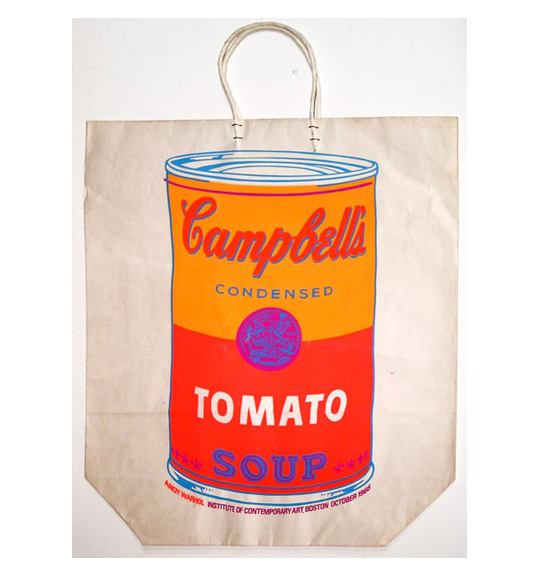 A photograph of a paper bag with a Campbell's tomato soup can picture on it, The can is yellow and red, with a purple logo in the center. The paper bag is white and flat, with white handles.