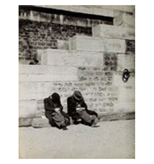 A black and white image of a brick wall and steps. Two men wearing hats are sitting between the steps, with their heads bowed down.