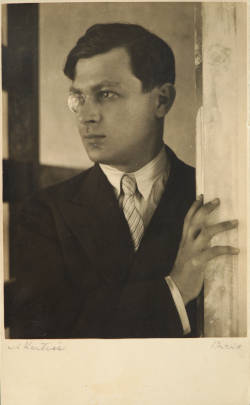 A photograph of a man with dark hair standing with one hand on what appears to be a doorway. He wears a dark suit, striped tie, and a monocle over his right eye as he gazes to the left.